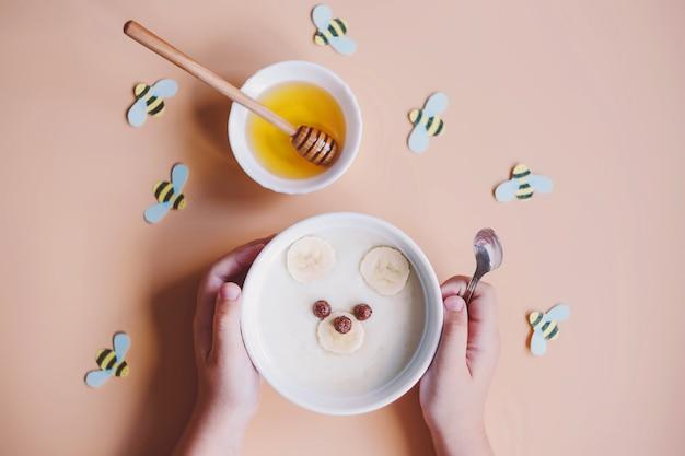 子供のための面白い朝食用食品。クマの形をした赤ちゃんのお粥、バナナ