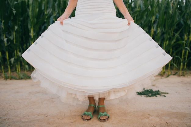 Funny bride in white wedding dress wearin green sandals and standing on the dusty road.