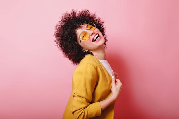Divertente donna brillante con brevi boccoli vestito giacca gialla e occhiali gialli sciocchi sul rosa