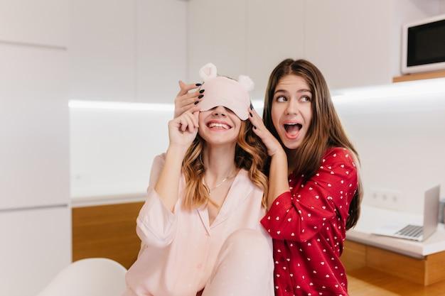 친구와 농담하는 동안 긍정적 인 감정을 표현하는 재미있는 갈색 머리 소녀. 함께 웃고있는 나이트 슈트에 멋진 백인 자매의 사진.