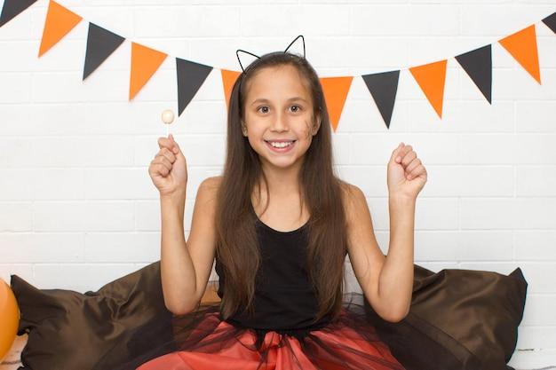 Смешная брюнетка в костюме ведьмы на хэллоуин с кошачьими ушами держит леденец и улыбается