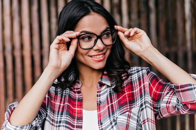 目をそらして笑っている面白いブルネットの少女。眼鏡をかけたかわいい幸せな女性の屋外の肖像画は、市松模様のシャツを着ています。