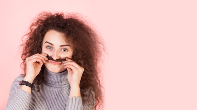 Funny brunette girl portrait on pink background