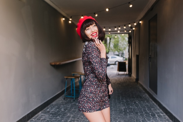 Funny brunette girl in trendy french red beret playfully posing with cute smile, touching her chin. adorable young dark-haired woman in short vintage dress having fun after work and laughing