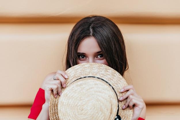 通りで麦わら帽子でポーズをとって暗い目を持つ面白いブルネットの少女。ポジティブな感情を表現する官能的な茶色の髪の女性。