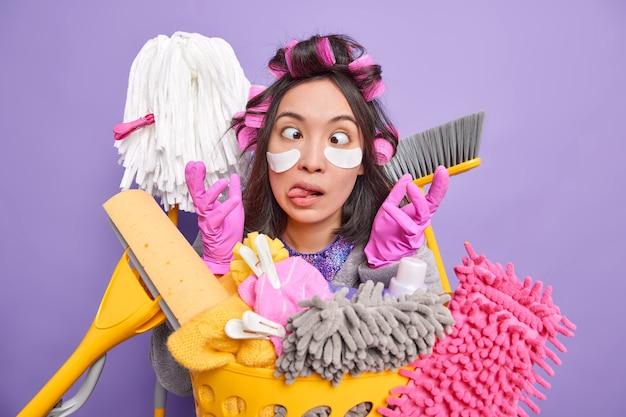 面白いブルネットの主婦は面白いしかめっ面を作ります目を交差させます舌を突き出します手袋で手を上げます紫色の背景の上に隔離された洗濯かごの近くの目のポーズの下にコラーゲンパッチを適用します