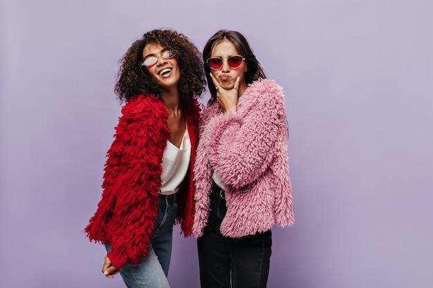 Una divertente signora bruna in abiti rosa lanuginosi e occhiali da sole rossi in posa con una ragazza riccia fresca in maglione rosso caldo e jeans