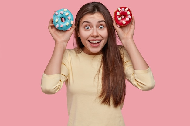 Funny brunette lady woman holds colourful doughnuts, looks happily directly