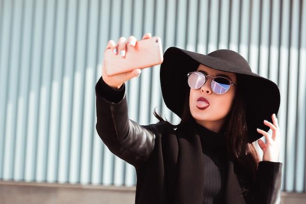 面白いブルネットモデルは、トレンディな帽子とサングラスを身に着けて、楽しんで、携帯電話で自分撮りをしています