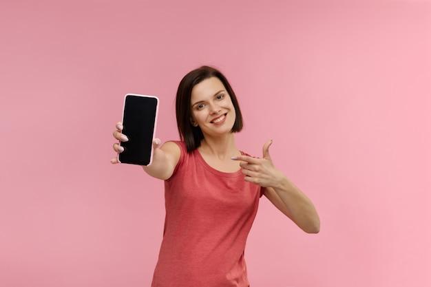 Смешная брюнетка женщина показывает пустой экран мобильного телефона на камеру