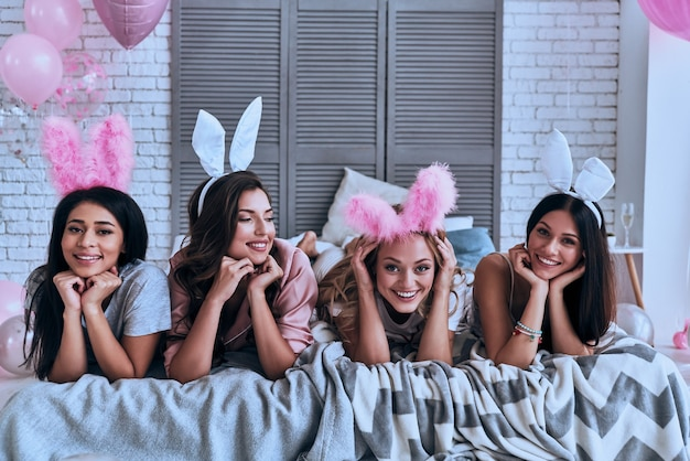 재미있는 토끼. 침대에 누워있는 동안 웃고있는 토끼 귀에 4 명의 쾌활한 젊은 여성