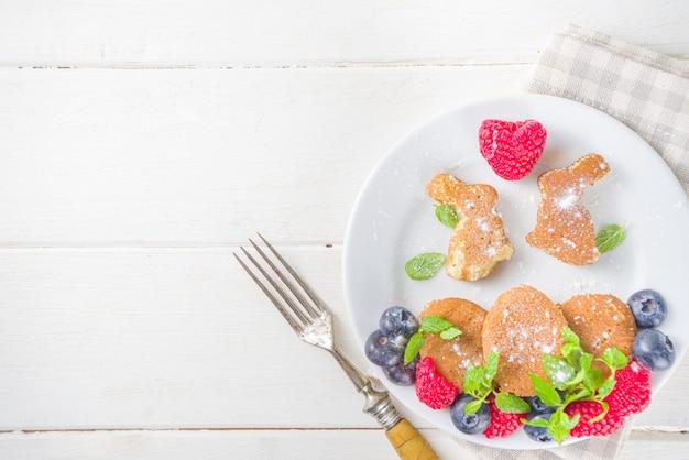 面白いバニーパンケーキ、イースターの朝のかわいいキッズ朝食。新鮮なベリーの装飾が施された創造的なウサギのパンケーキ、白い木製の背景のコピースペースの上面図