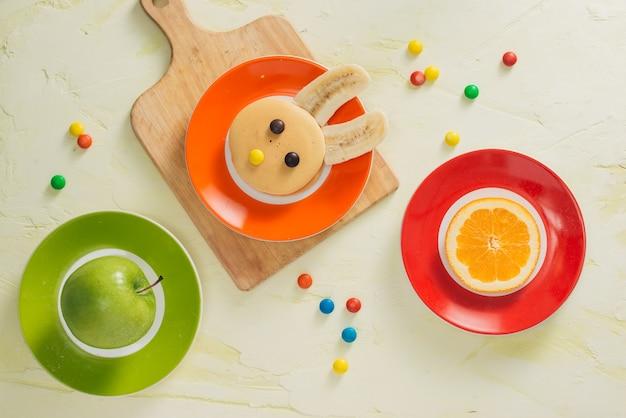 부활절 어린이 아침 식사를위한 과일과 함께 재미있는 토끼 팬케이크