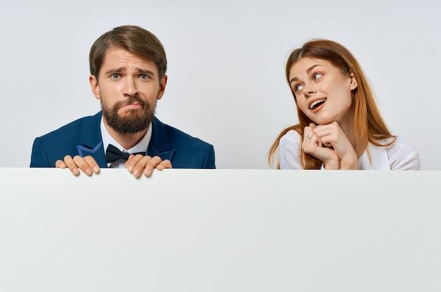 プロモーションポスターを保持している面白いビジネスの男性と女性