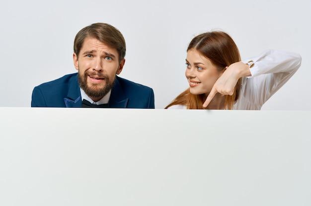 白いバナーを宣伝する面白いビジネスの男性と女性のプレゼンテーション
