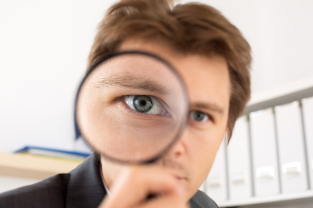 虫眼鏡の肖像画を保持している面白いビジネスマン。私立探偵の調査、層、犯罪、ビジネス研究またはセキュリティの概念
