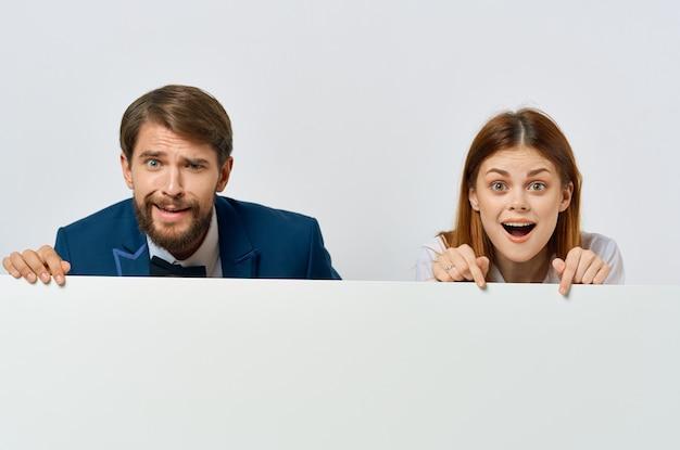 面白いビジネスマンと広告の白いバナーを提示する女性。