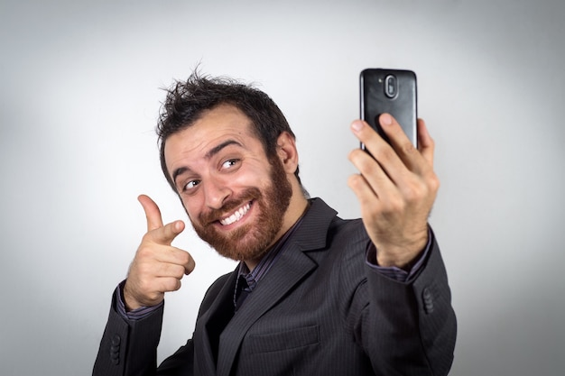 Funny businessman is using his smartphone to take a selfie