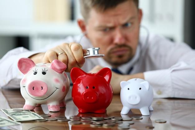 Funny businessman listen three piggybanks for cash