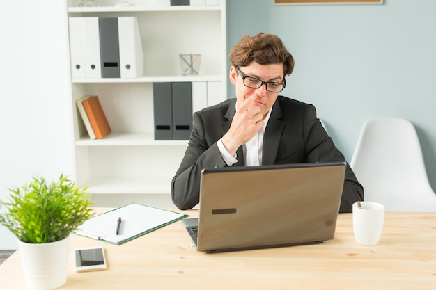 Funny businessman picking his nose in office space