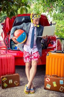 Забавный бизнесмен готов к поездке человек, стоящий возле красной машины летние каникулы и концепция путешествий