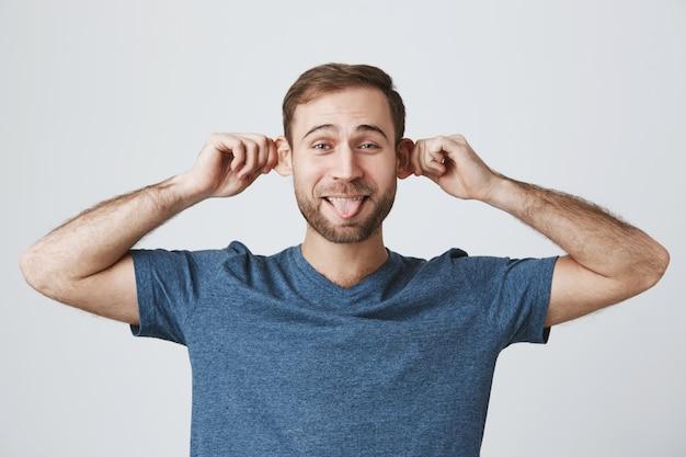 Divertente ragazzo barbuto spensierato che tira le orecchie e mostra la lingua sciocca