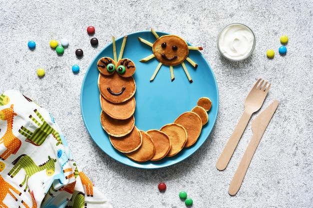 눈을 가진 재미있는 애벌레. 팬케이크 애벌레, 재미있는 아이 아침 식사.