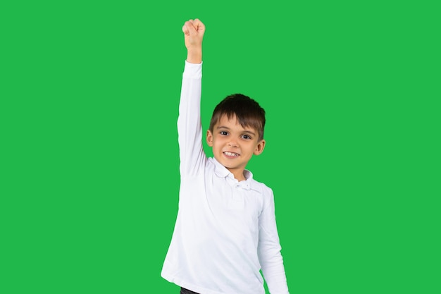 白いシャツを着た面白い白人の少年は勝利のために彼の拳を持ち上げます