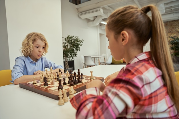 Funny caucasian boy looking emotional while playing chess with his friend sitting at the table in