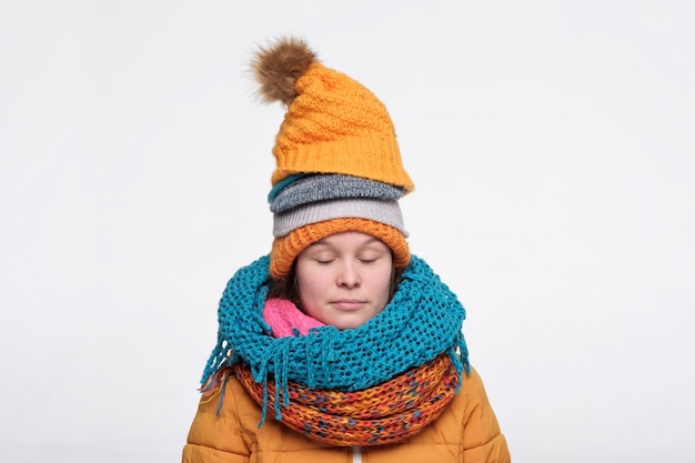 いくつかのスカーフと帽子が目を閉じてリラックスできる面白い白人女性10代。