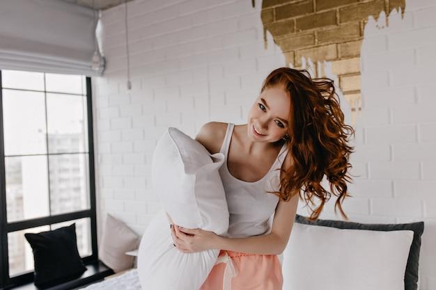 朝にふざけてポーズをとる枕を持つ面白い白人女性。洗練されたヨーロッパの巻き毛の女の子enjoiyng写真撮影。