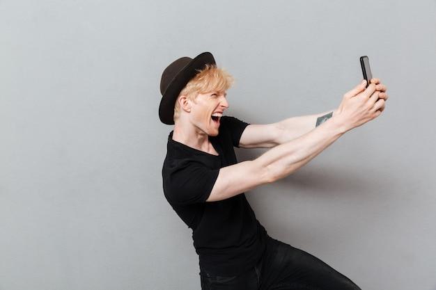 Funny caucasian man make selfie by mobile phone.