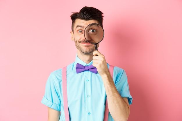 ピンクの背景の上に立って、大きな目で虫眼鏡を通して見て、笑顔で、口ひげと蝶ネクタイを持つ面白い白人男性。