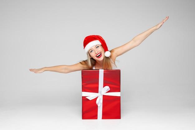 面白い白人女性は贈り物と大きな赤い箱で飛行機を描いています