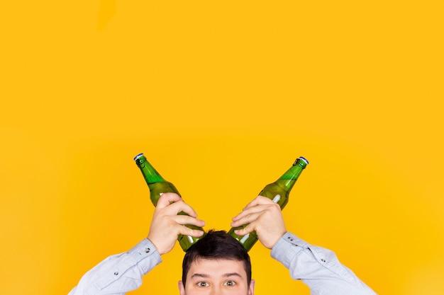 Забавный харизматичный человек с бутылками рогов на желтой стене