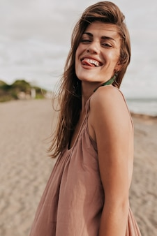 갈색 머리를 가진 재미있는 매력적인 아가씨가 얼굴을 만들고 햇빛에 해변에서 재미