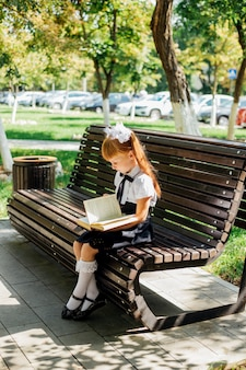 Funny charming little girl with books in her hands, on the first day of school or kindergarten. a child is sitting on a bench outside on a warm sunny day, and is returning to school.