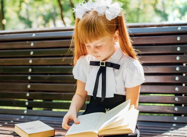 Забавная очаровательная маленькая девочка с книгами в руках, в первый день в школе или детском саду. в теплый солнечный день ребенок сидит на скамейке на улице и возвращается в школу.