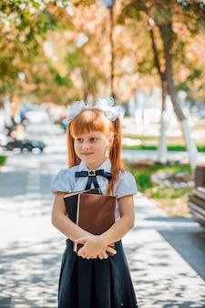 학교나 유치원 첫날에 손에 책을 들고 있는 재미있는 매력적인 어린 소녀.