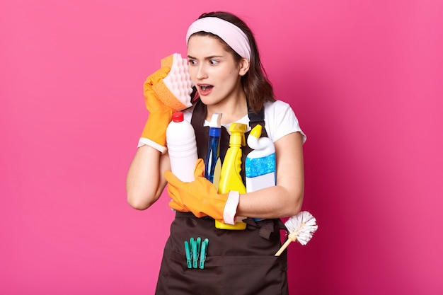 Funny charming young caucasian housewife wearing casual t shirt and apron, orange rubber gloves, holding sponges at her face, imagines that is phone, has fun while doing chores. hygiene concept.