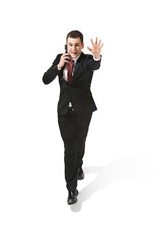 Uomo d'affari allegro divertente che va con il telefono cellulare sopra bianco. felice giovane uomo in tuta. affari, carriera, successo, concetto di vittoria