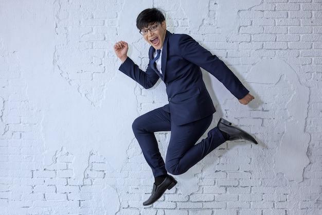 Забавный веселый бизнесмен прыгает в воздухе над белой стеной
