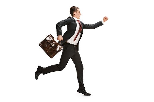 ホワイトスタジオの背景の上を実行している面白い陽気なビジネスマン。スーツで幸せな若い男。ビジネス、キャリア、成功、勝利のコンセプト。勝利、喜び。人間の顔の感情