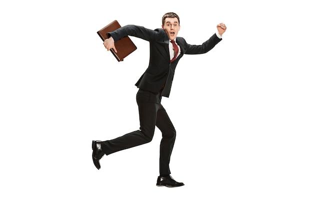 Uomo d'affari allegro divertente che funziona sopra il fondo bianco dello studio.