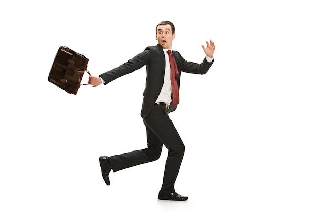 Funny cheerful businessman running over white studio background.