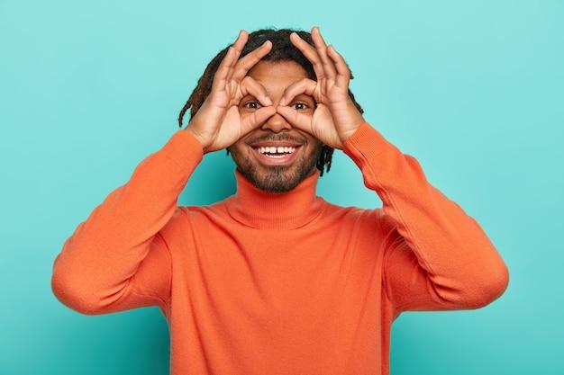 웃기는 쾌활한 남자가 눈 근처에 손을 잡고 쌍안경을 통해 보는 척하고 향취가 파란색에 고립 된 오렌지 터틀넥을 착용하고 있습니다.