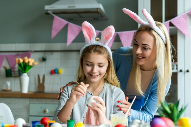 Funny, cheerful, joyful mum teaching, training her cute, pretty, small, little daughter draw, paint, decorate easter eggs, together wearing bunny ears, preparing for easter