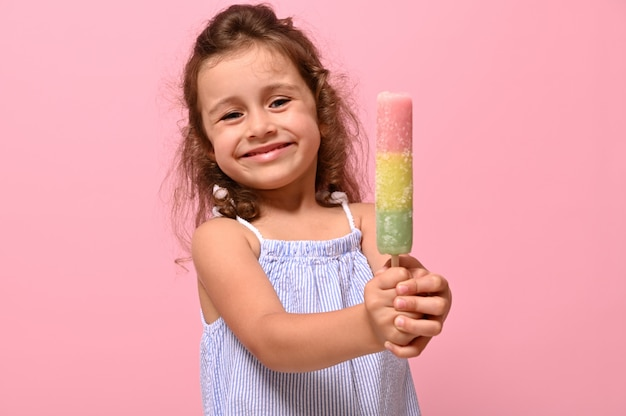 面白い陽気な少女の笑顔がカメラにおいしい甘い冷凍ジュース、アイスキャンディー、アイスクリームを手に見せています。広告のための夏のコンセプト、ピンクの背景、プロモーションのためのコピースペース