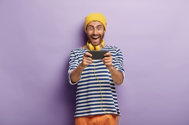 Funny cheerful male gamer plays video games via smartphone, wears yellow hat and striped jumper, being addicted to modern technologies, isolated on purple wall, checks out new application