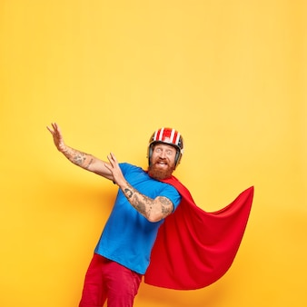 面白い陽気な男性のスーパーヒーローはヘルメットと赤いマントを着ています